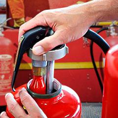Especialista finalizando el mantenimiento y recarga de un extintor