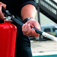Especialista descargando el agente extintor de un cilindro para su posterior recarga
