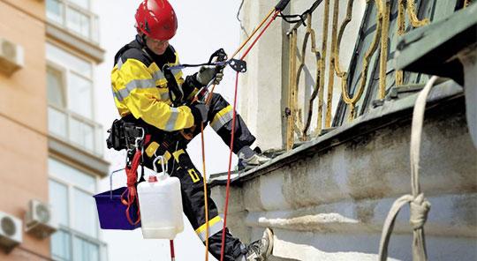 Personal laborando con equipo de protección para alturas y sistema de rescate.