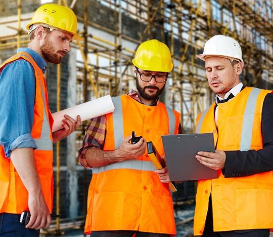 Trabajadores utilizando equipo de protección personal en una construcción.