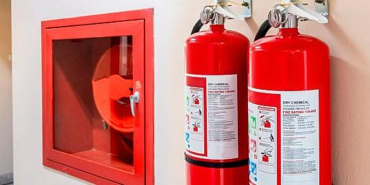 Foto de unos extintores portátiles colgados en la pared.