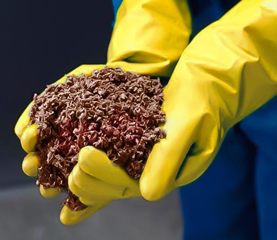 Personal mostrando tierra contaminada por derrame de hidrocarburos.