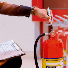 Especialista revisando el mantenimiento y recarga terminado de un extintor.