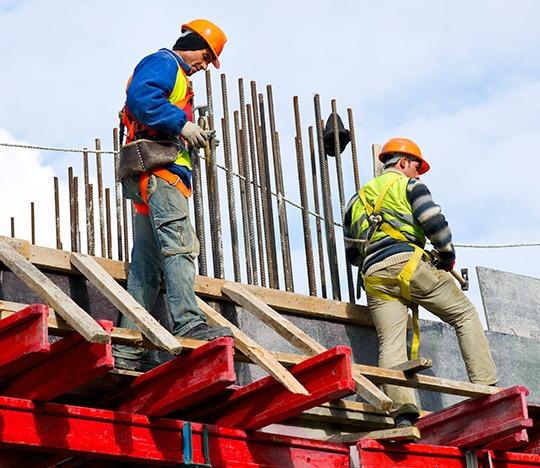 Trabajadores usando equipo de Seguridad Industrial en las alturas.